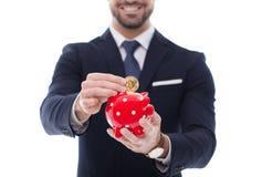 Bitcoin de la baisse une d'homme d'affaires dans la tirelire d'isolement Photographie stock libre de droits