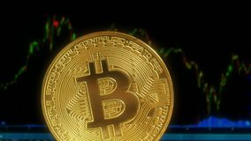 Bitcoin de la moneda de oro, contra la perspectiva de la exhibición con un gráfico de citas de crypto-monedas Comercio adentro almacen de metraje de vídeo