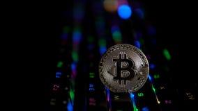 Bitcoin de la moneda de plata en el fondo de un teclado que destella almacen de video