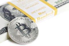 Bitcoin de la moneda y paquete del banco de 100 dólares Foto de archivo libre de regalías
