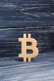 Bitcoin de madera en un fondo de tableros negros Moneda Crypto, bloqueando tecnología El hundimiento y la subida del coste de bit imagenes de archivo
