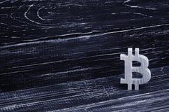 Bitcoin de madera en un fondo de tableros negros Moneda Crypto, bloqueando tecnología El hundimiento y la subida del coste de bit foto de archivo