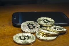 Bitcoin - de muntstukken groepeerden zich dichtbij de celtelefoon Houten achtergrond Stock Fotografie