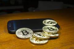 Bitcoin - de muntstukken groepeerden zich dichtbij de celtelefoon Houten achtergrond Royalty-vrije Stock Foto