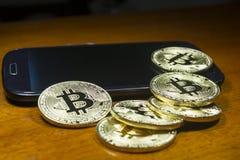 Bitcoin - de muntstukken groepeerden zich dichtbij de celtelefoon Houten achtergrond Stock Afbeelding