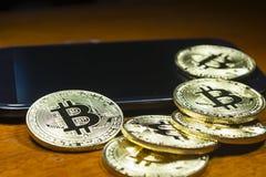 Bitcoin - de muntstukken groepeerden zich dichtbij de celtelefoon Houten achtergrond Stock Afbeeldingen