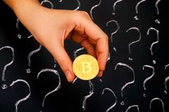 Bitcoin de oro en mano de la mujer contra la pizarra con la pregunta mA Imagen de archivo