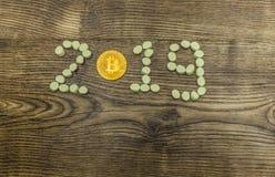 Bitcoin de oro y melcochas que forman el texto 2019 en la madera Imagen de archivo