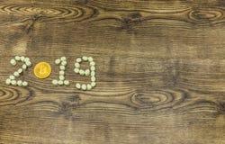 Bitcoin de oro y melcochas que forman el texto 2019 en la madera Fotografía de archivo