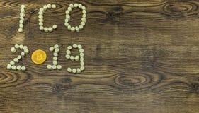 Bitcoin de oro y melcochas que forman el texto de ICO 2019 en la madera Imágenes de archivo libres de regalías