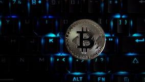 Bitcoin de pièce en argent sur le fond d'un clavier de clignotant banque de vidéos