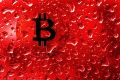Bitcoin de pièce de monnaie derrière le verre avec des baisses rouges photographie stock
