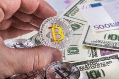 Bitcoin de pièces de monnaie sur le fond des billets de banque des dollars et de l'euro Photos stock
