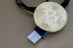Bitcoin del kriptonite di Digital con un cavo di USB su un fondo bronzeo fotografie stock libere da diritti