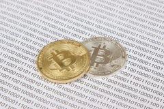 Bitcoin dell'argento e dell'oro sui precedenti del codice binario Fotografia Stock