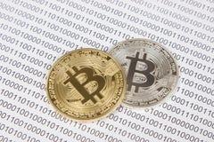 Bitcoin dell'argento e dell'oro sui precedenti del codice binario Fotografie Stock