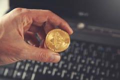 Bitcoin della mano dell'uomo con la tastiera immagine stock