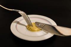 Bitcoin della moneta di oro sul piatto con il coltello e forcella isolata su fondo nero immagine stock libera da diritti