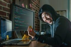 Bitcoin della tenuta del pirata informatico e guardare vizioso immagini stock libere da diritti