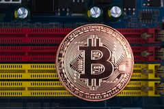 Bitcoin digital currency,  bit-coin on motherboard or electronic Royalty Free Stock Images