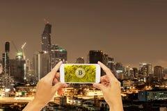 Bitcoin do ouro no telefone esperto da tela com construção em Banguecoque foto de stock royalty free
