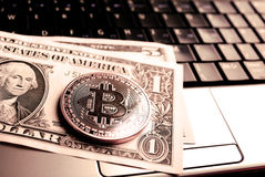 Bitcoin on dollar bill over laptop Royalty Free Stock Photography
