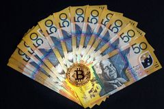 Bitcoin dorato che emette luce sopra l'australiano le banconote di 50 dollari su fondo nero Fotografia Stock