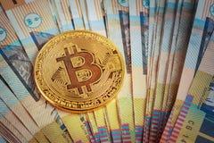 Bitcoin dorato che emette luce sul mucchio dell'australiano le banconote di 50 dollari Immagine Stock