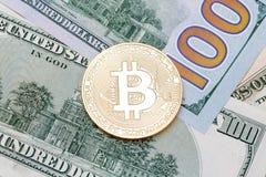 Bitcoin dorato di cryptocurrency sulle banconote degli Stati Uniti Fotografia Stock