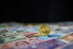 Bitcoin dorato sopra il fondo internazionale della banconota, nuovo fotografie stock libere da diritti