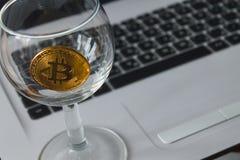Bitcoin dorato in un vetro sul fondo del computer portatile Immagini Stock Libere da Diritti