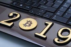 Bitcoin dourado Encontra-se no portátil Inscrição 2019 imagem de stock royalty free