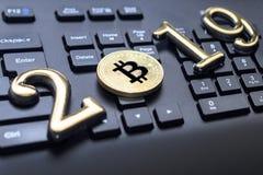 bitcoin dourado encontra-se no teclado de uma cor escura A inscrição 2019 Há uma tonificação foto de stock