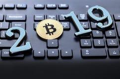 bitcoin dourado encontra-se no teclado de uma cor escura A inscrição 2019 Há uma tonificação imagem de stock royalty free