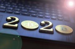 bitcoin dourado encontra-se no teclado de uma cor escura A inscrição 2020 Há uma tonificação imagens de stock