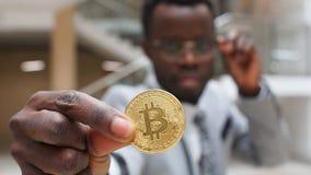 Bitcoin dourado na mão africana do homem Homem de negócios Holding Digitall Symbol da moeda virtual nova filme
