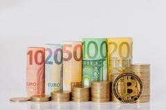 Bitcoin, Dziesięć, dwadzieścia, pięćdziesiąt, sto, dwieście i moneta euro staczający się, wystawiamy rachunek banknoty na białym  zdjęcia stock