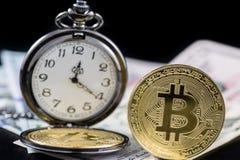 Bitcoin e orologio da tasca dorati vicino sui dollari americani Immagine Stock Libera da Diritti