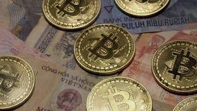 Bitcoin en diversos billetes de banco asiáticos que giran en placa giratoria Moneda internacional de Asia Moneda de Digitaces y metrajes