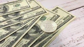 Bitcoin en dollars Het platinamuntstuk bitcoin ligt op honderd-dollar rekeningen Blockchain is de technologie van de toekomst stock footage
