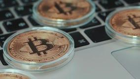 Bitcoin en el teclado Moneda de Bitcoin con concepto del blockchain en el teclado del ordenador portátil con las monedas y cartas almacen de metraje de vídeo