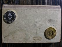 Bitcoin et Ethereum sur un vieux livre se trouvant sur une table en bois nouvel argent virtuel