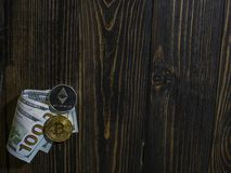 Bitcoin and Ethereum on banknotes of hundred dollars on a wooden background. Conceptual image for worldwide cryptocurrency and royalty free stock images