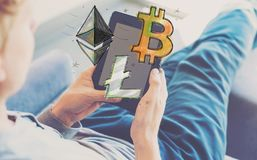 Bitcoin Ethereum and Litecoin text with man using a tablet. Bitcoin Ethereum and Litecoin with man using a tablet in a chair Stock Images
