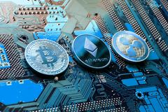 Bitcoin, Ethereum, Ripple coins on computer motherboard, cryptocurrency investing concept. Bitcoin, Ethereum and Ripple coins - largest cryptocurrencies by royalty free stock photo