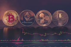 Bitcoin, Ethereum, Ripple and Litecoin. Cryptocurrency with stock charts. Bitcoin, Ethereum, Ripple and tecoin - Cryptocurrency coins with stock charts on wood royalty free stock photos