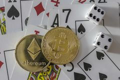 Bitcoin and etherium token with cards and dice. A bitcoin and etherium token with cards and dice royalty free stock photos