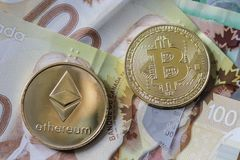 Bitcoin and Etherium Token on Cash. A gold Bitcoin and Etherium Token on Canadian Cash royalty free stock images