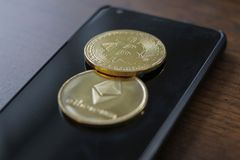 A bitcoin and etherium token on a cell phone.  royalty free stock photos