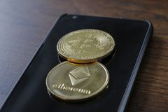 A bitcoin and etherium token on a cell phone.  stock images